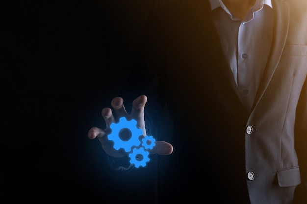 Hombre de negocios en traje sosteniendo engranajes metálicos y mecanismo de ruedas dentadas que representa el trabajo en equipo de interacción