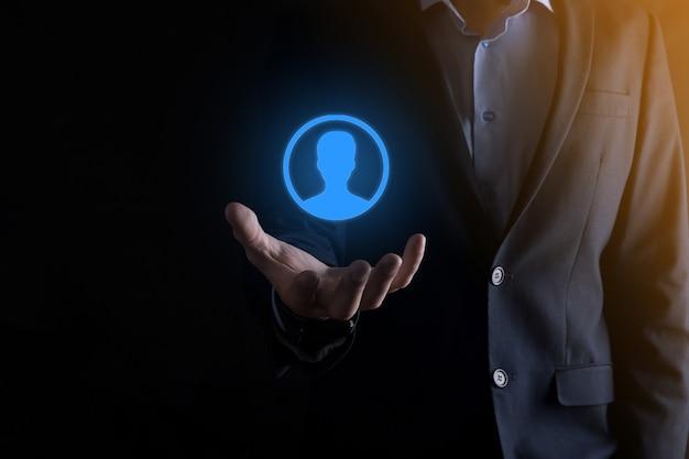 Hombre de negocios en traje sosteniendo el icono de la mano del usuario. primer plano de la interfaz de los iconos de internet. concepto de medios de red global, contacto en pantallas virtuales, espacio de copia.