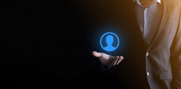 Hombre de negocios en traje sosteniendo el icono de la mano del usuario. primer plano de la interfaz de los iconos de internet