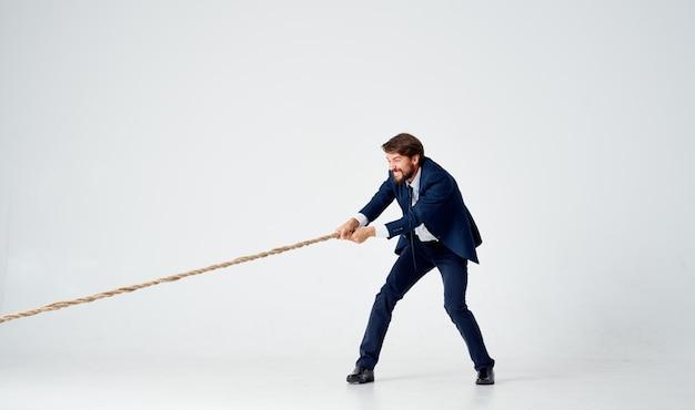 Hombre de negocios en un traje tira de la cuerda de fondo claro de estudio