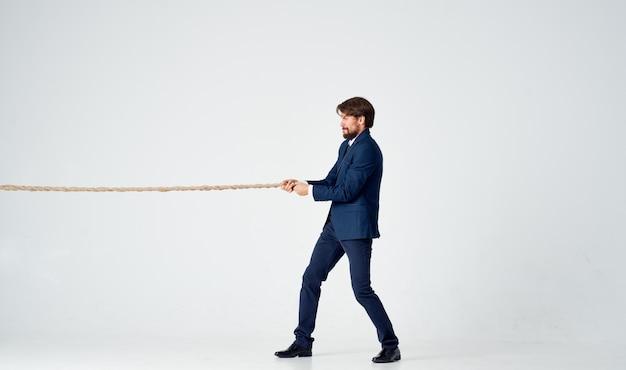 Hombre de negocios en traje tira de una cuerda sobre un fondo claro