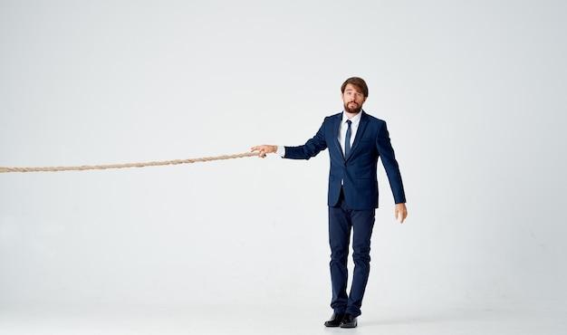 Hombre de negocios en traje tira de una cuerda