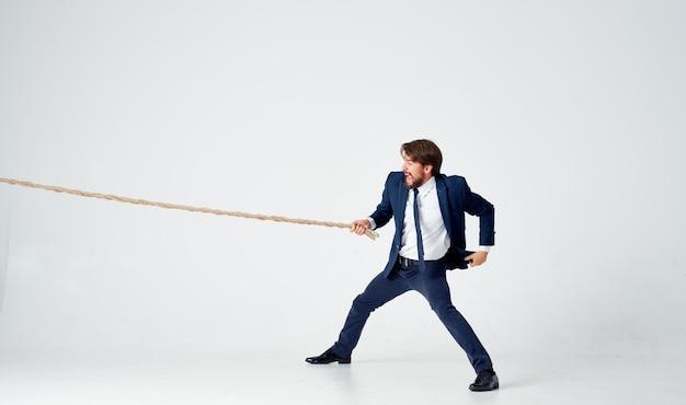 Hombre de negocios en traje tirando de la cuerda de trabajo en equipo de estudio