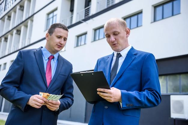 Hombre de negocios en trajes hacer trato con los billetes en euros