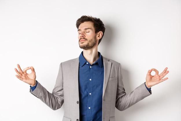 Hombre de negocios tranquilo y concentrado meditando con los ojos cerrados y las manos extendidas hacia los lados, encontrando la paz en la meditación, practicando la respiración del yoga, de pie sobre un fondo blanco.
