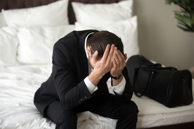 Hombre de negocios trastornado subrayado que se sienta en cama, teniendo dolor de cabeza.