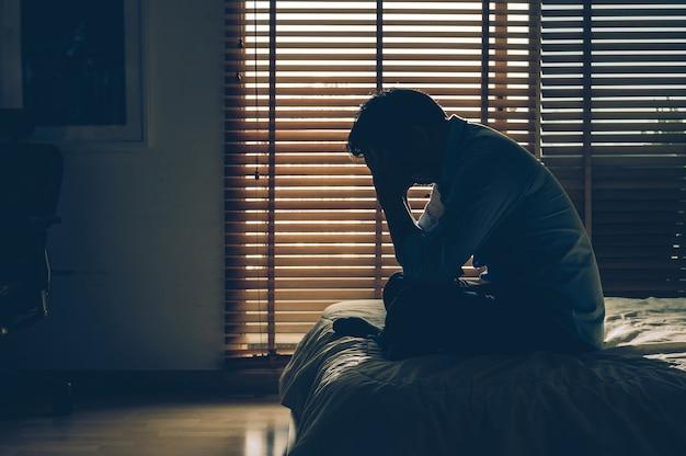 Hombre de negocios triste que se sienta la cabeza en las manos en la cama en el dormitorio oscuro