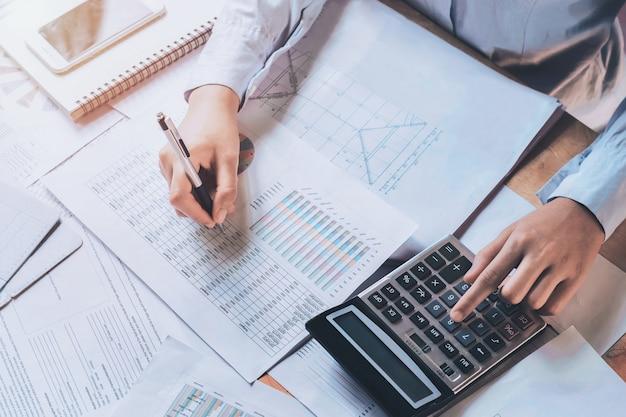 Hombre de negocios usando la calculadora para calcular el presupuesto.