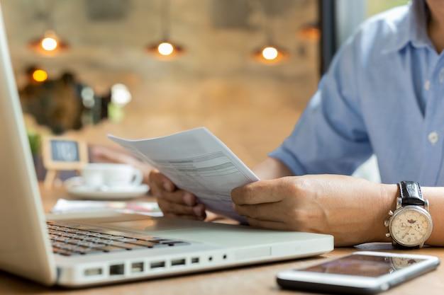 Hombre de negocios usando la computadora portátil mientras mira factura.