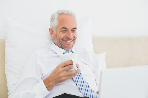 Hombre de negocios usando la computadora portátil mientras tomando un café en la cama
