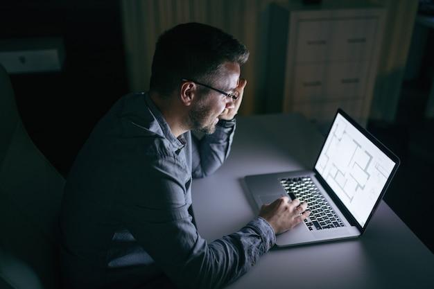 Hombre de negocios usando la computadora portátil y sentado en la oficina por la noche.