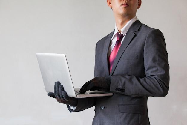 Hombre de negocios usando guantes y usando la computadora - fraude, pirata informático, robo, concepto de delito cibernético
