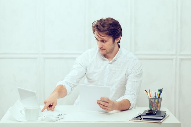 Hombre de negocios usando laptop con tableta y lápiz