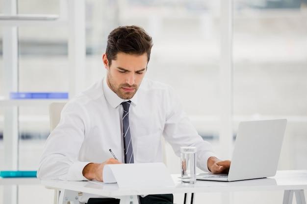 Hombre de negocios usando laptop y tomar notas