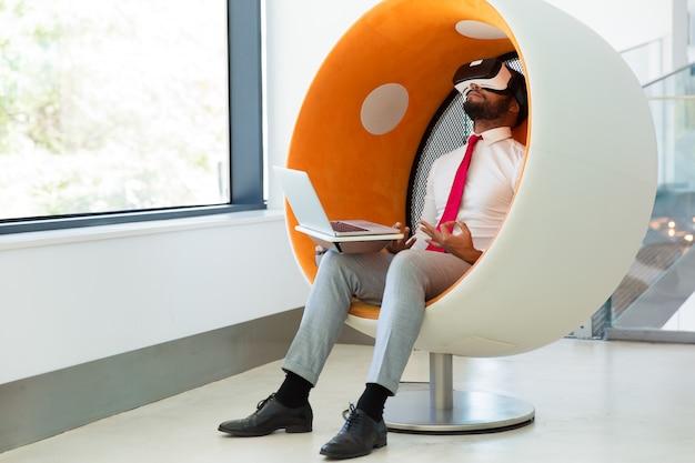 Hombre de negocios usando el simulador de realidad virtual para meditar