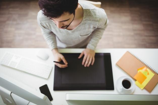 Hombre de negocios usando tableta gráfica en oficina creativa