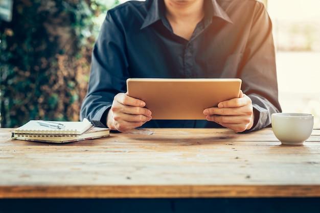Hombre de negocios usando la tableta en la mesa de madera en la cafetería.