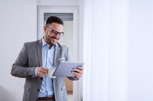 Hombre de negocios usando tableta y sosteniendo café.