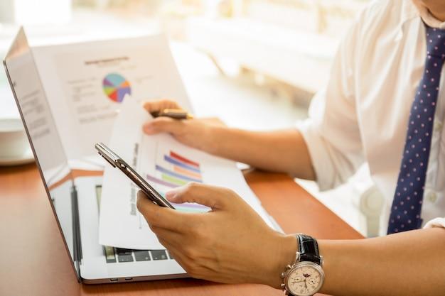 Hombre de negocios usando el teléfono celular y sosteniendo el informe gráfico financiero en la tabla.
