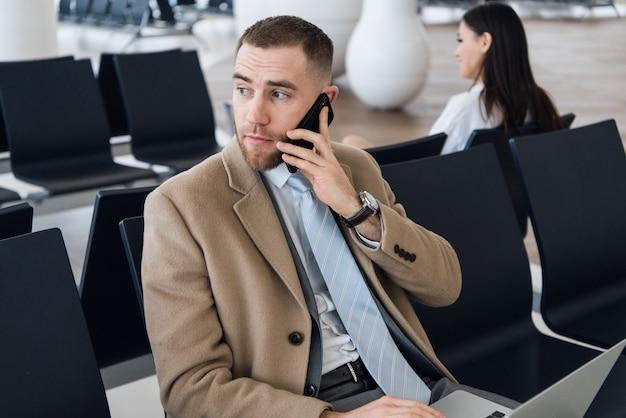 Hombre de negocios usando teléfono inteligente dentro del edificio de oficinas o aeropuerto.