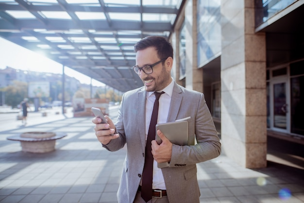 Hombre de negocios usando el teléfono inteligente para leer / escribir mensajes de texto mientras está de pie delante del centro de negocios. en otra mano tableta.