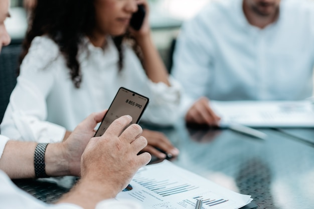 Hombre de negocios usando un teléfono inteligente mientras trabaja con documentos financieros