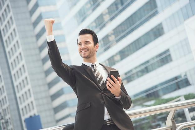 Hombre de negocios usando el teléfono móvil y sonriendo feliz emocionado y levantando su brazo.