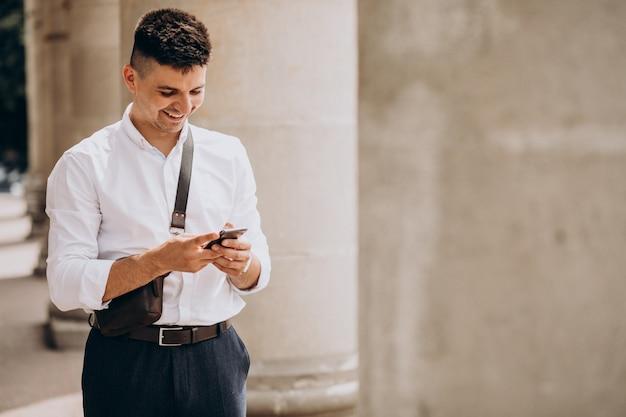 Hombre de negocios usando el teléfono por la universidad