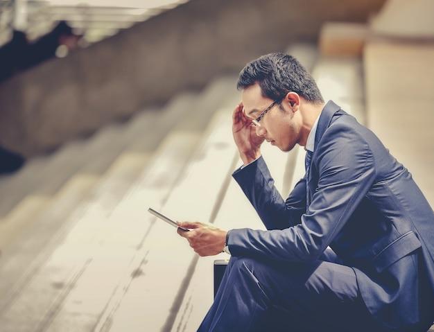 El hombre de negocios utiliza la tableta para trabajar en todas las partes de la ciudad
