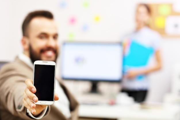 Hombre de negocios, utilizar, smartphone, en, oficina