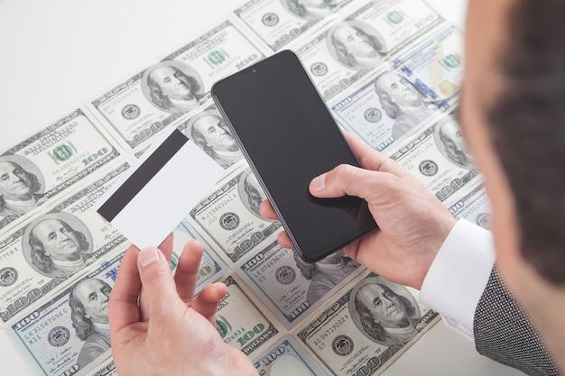 Hombre de negocios, utilizar, smartphone, y, tenencia, tarjeta de crédito