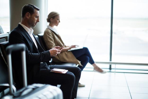 Hombre de negocios, utilizar, teléfono móvil, en, área de espera