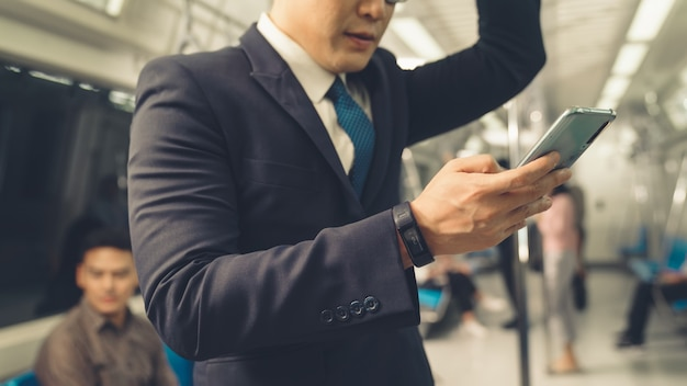 Hombre de negocios, utilizar, teléfono móvil, en, tren público