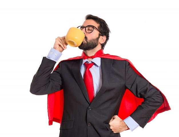 Hombre de negocios vestido como superhéroe bebiendo café