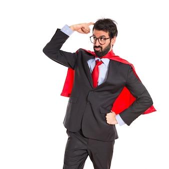 Hombre de negocios vestido como superhéroe pensando sobre blanco