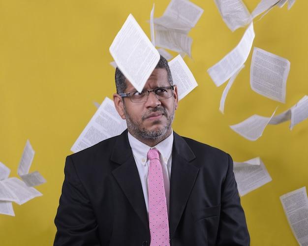 Hombre de negocios vestido con corbata y traje, confundido en medio de papeles voladores