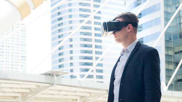 Hombre de negocios con vidrio vr para soporte de smartphone en al aire libre.