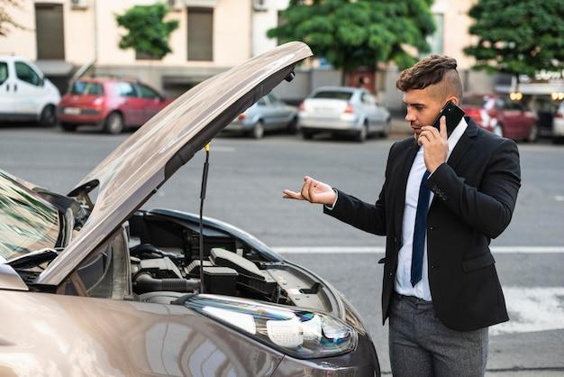 Hombre de negocios de vista lateral hablando con el servicio de coche