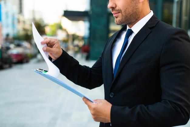 Hombre de negocios de vista lateral leyendo desde un portapapeles