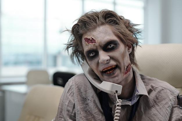 Hombre de negocios zombie feo hablando por teléfono en el lugar de trabajo en la oficina