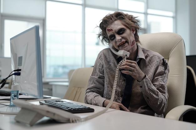 Hombre de negocios zombie con receptor de teléfono entre el hombro y la mejilla mirando la pantalla de la computadora y hablando con alguien en la oficina