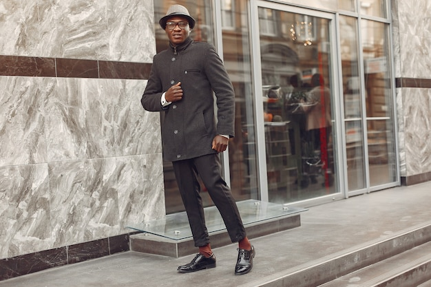 Hombre negro con un abrigo negro en una ciudad de otoño
