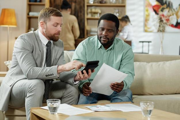Hombre negro adulto y asesor financiero calculando la tasa de hipoteca sentado en el sofá en casa