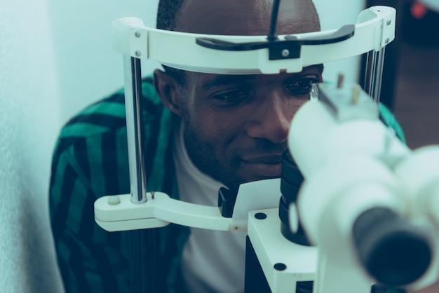 Hombre negro adulto en oftalmólogo en clínica