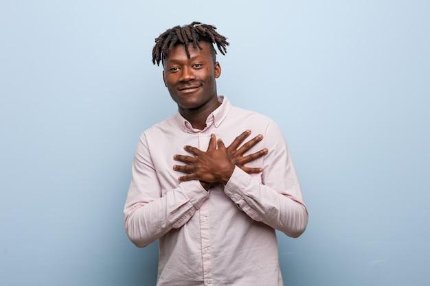 El hombre negro africano joven del negocio tiene expresión amistosa, presionando la palma contra el pecho. amor .