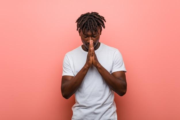 El hombre negro africano joven que lleva a cabo las manos en ruega cerca de boca, se siente confiado.
