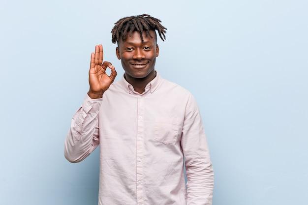 Hombre negro africano del negocio joven alegre y confiado que muestra gesto aceptable.