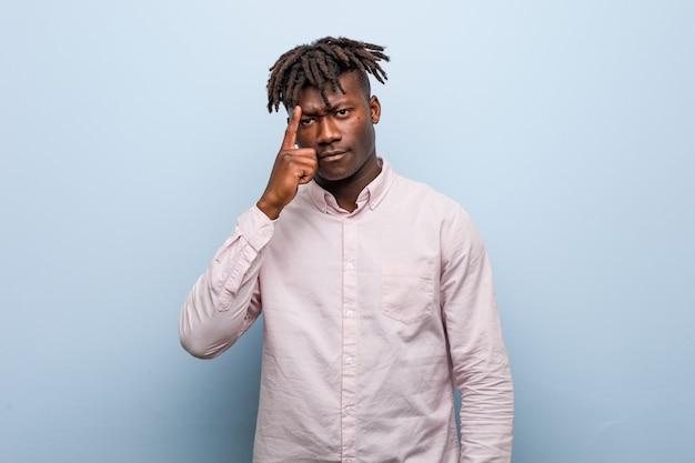 Hombre negro africano del negocio joven que señala el templo con el dedo, pensando, centrado en una tarea.
