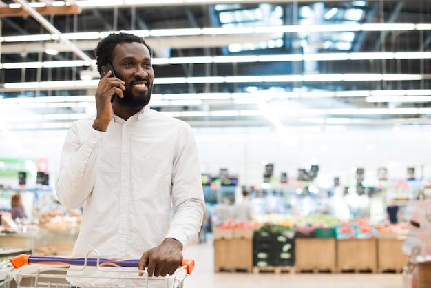 Hombre negro alegre que habla en el teléfono celular en la tienda de comestibles