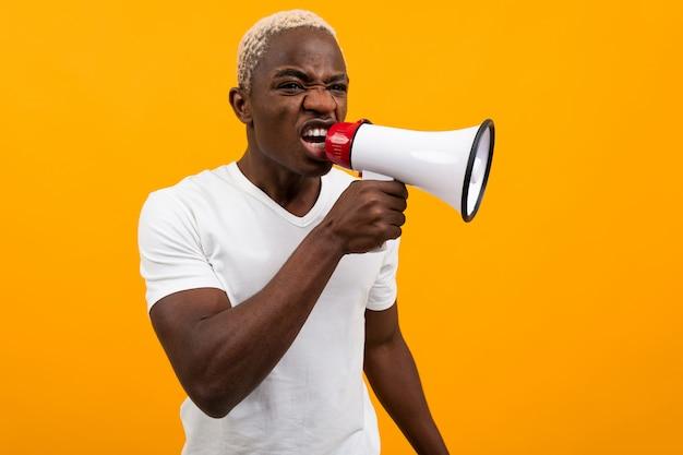 Hombre negro americano en una camiseta blanca cantando en un megáfono sobre un fondo naranja aislado